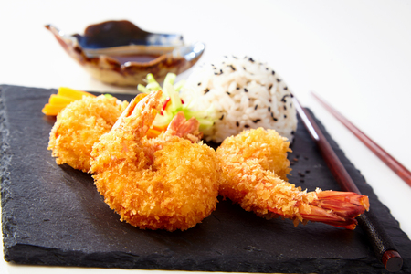 Seafood appetizer with crispy fried golden Japanese tempura batter shrimp served with rice on a black slate slab Stock Photo