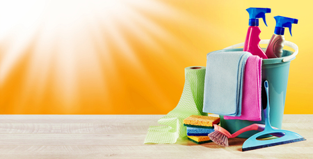 Summer sunburst in a hot orange sky with domestic cleaning supplies arranged neatly to the side in panorama banner format and copy space for advertising Foto de archivo