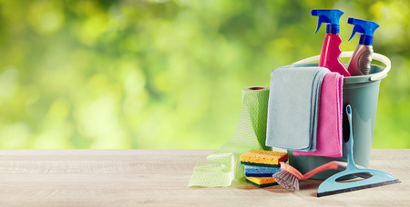 Plastic bucket with domestic cleaning supplies outdoors on a rustic wooden table against blurred greenery with copy space in a panorama banner