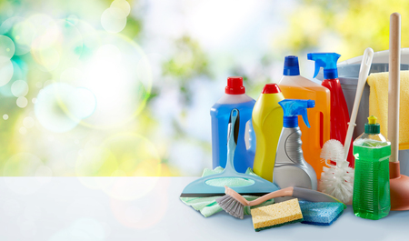 Sanitation and cleaning supplies on a table at home with assorted plastic bottles and sprayers, sponges, cloths, toilet brush and plunger with high key outdoor background and copy space