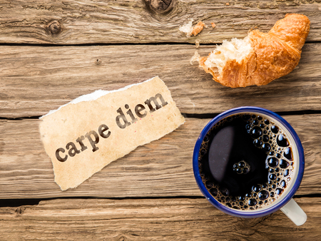 Carpe Diem, or Seize the Day, inspirational and motivational message on torn paper alongside a mug of hot espresso coffee and half eaten croissant in a top down view on rustic wood