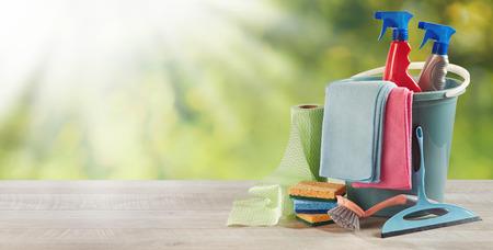 Artículos de limpieza para el hogar en una mesa de jardín rústica con rayos de sol de verano sobre vegetación y espacio de copia en un concepto de higiene o limpieza de primavera Foto de archivo