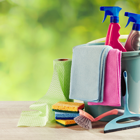 Selection of household cleaning products in a plastic bucket with sponges and paper towel alongside on a garden table with blurred greenery and copy space in square format