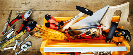 Colorful yellow tool box with assorted DIY hand tools for renovation, woodworking or construction on a rustic wood background Stock Photo