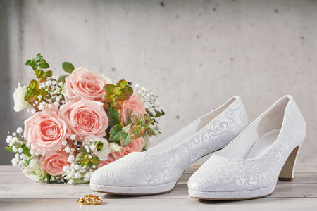 Bouquet of beautiful pink roses next to fancy sparkling wedding shoes standing in front of spotted wall