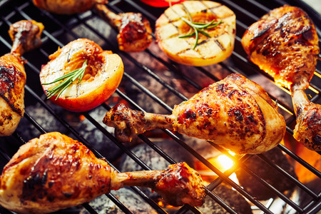 Spicy chicken legs sizzling over a hot barbecue with halved fresh apricots or nectarines seasoned with rosemary in a close up view