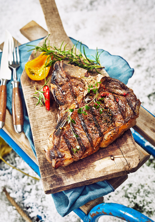 Seasoned grilled T-bone steak at a winter BBQ served with herb garnish on a wooden board on top of a small toboggan outdoors in fresh snow in a close up high angle view