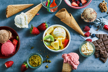 Flat lay of assorted ice cream served in bowls and cones with fresh fruit and nut ingredients, choclate bar and flakes and a metal scoop viewed from overhead