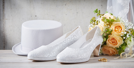 White sparkly wedding shoes next to romantic orange flower bouquet and tall bright white hat in front of dirty wall