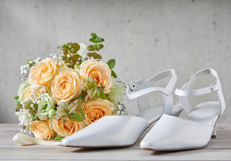 Stylish modern white pointed toe wedding shoes with straps in classic white leather alongside a bridal bouquet of fresh orange roses with copy space above