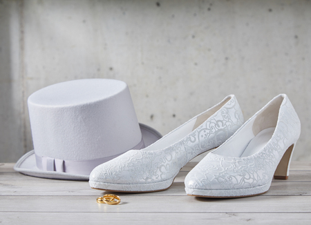 White wedding top hat sitting next to decorated bridal accessory shoes in front of dirty spotted wall Archivio Fotografico - 107768322