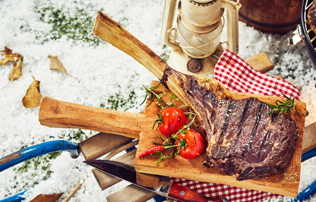 Grilled rib steak or chop with bone-in with roasted tomatoes and chili pepper on a rustic wooden board on a toboggan outdoors in winter snow for a seasonal barbecue Standard-Bild - 107768393