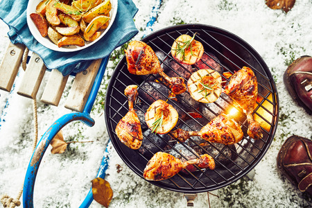 Tasty spicy marinated chicken legs on a barbecue grilling over the hot coals outdoors on a cold winter day with snow viewed from overhead Banque d'images - 107768398
