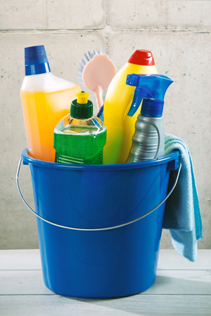 Blue plastic bucket filled with household cleaning supplies in plastic bottles, a scrubbing brush and cloth in a health and hygiene concept