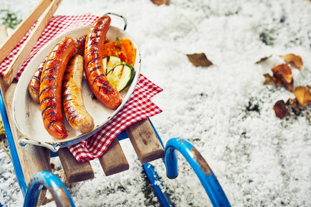 Succulent grilled pork sausages for a winter BBQ served in an aluminum dish on an old sled or toboggan in fresh snow scattered with dead leaves for copy space Standard-Bild - 107768401
