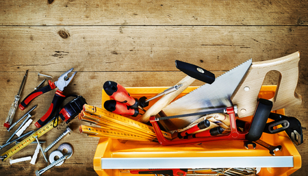 DIY and renovation concept with assorted hand tools in a yellow plastic box with scattered tools alongside on a rustic wood background with copy space Stock Photo