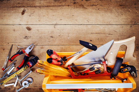 Top down view of hand tools in a colorful plastic yellow tool box with scattered tools alongside on a rustic wood background with vignette and copy space