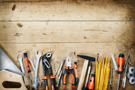 Bottom border of assorted hand tools arranged in a neat row conceptual of DIY, renovations, repair, building and woodworking over wood with copy space and vignette