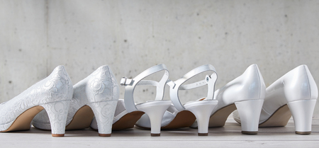 Line of three pairs of stylish white high heel shoes viewed from the back with the center pair having straps in a concept of wedding fashion with copy space above in panorama view Archivio Fotografico - 107768410