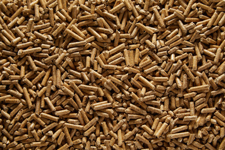 Background texture of renewable compressed wood pellets for use in household heating, barbecue or in the garden as a mulch around plants