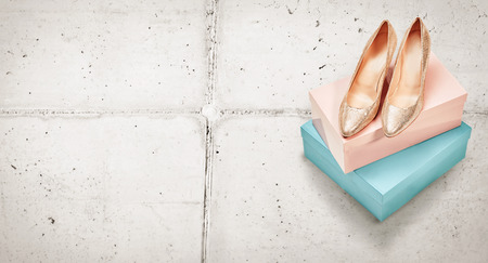 Pair of elegant metallic gold high heeled court shoes for evening wear displayed on top of two colorful boxes on paving stones viewed high angle with copy space