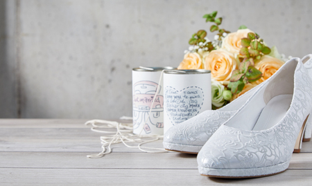 White bridal shoes next to two cans connected by string and orange flower bouquet standing on gray wooden table