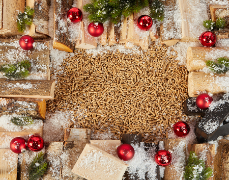 Winter Christmas frame with logs decorated with bright red festive baubles and pine sprinkled with fresh snow around central copy space on wood pellets for heating