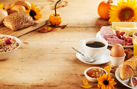 Healthy autumn breakfast borders on both sides of a rustic wood table with copy space, sunflowers , pumpkin and delicious fresh food with coffee Stock Photo