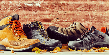 Rustic autumn panorama of assorted sneakers, shoes and leather boots with colorful leaves and wood background with copy space Stock Photo