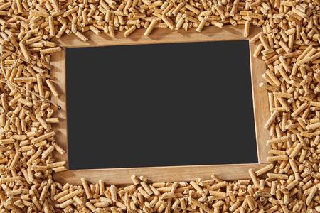 Pizarra de la vendimia de la escuela con espacio de copia en blanco rodeado de pellets de madera de aserrín compacto para la calefacción de la primavera y el saneamiento Foto de archivo - 108046938