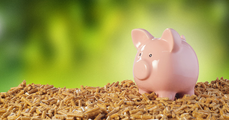 Pink piggy bank on a pile of wood pellets against a blurred outdoor green background conceptual of costs or savings of organic biofuels Stockfoto