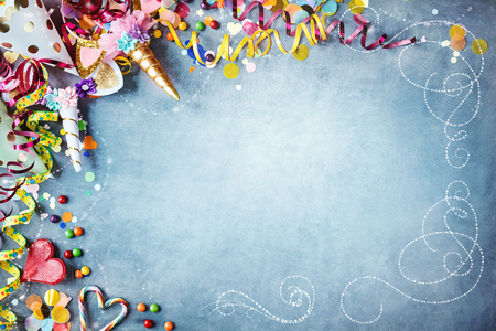 Decorative carnival party background with colorful hats, streamers, unicorn costumes, candy, confetti and hearts as a border against a textured blue background with vignette and copy space Stock Photo