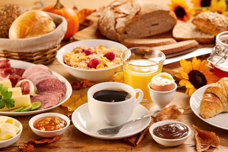 Table covered by assorted food and beverages including orange juice and croissant rolls on top of white plates