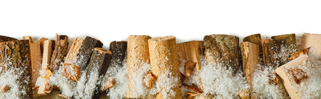 Panorama banner with logs of split wood and compressed sawdust with a scattering of winter snow and autumn leaves over white with copy space Stockfoto
