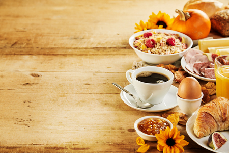 Seasonal autumn Intercontinental breakfast border with a variety of fresh food and beverages, sunflowers and pumpkins on a rustic wood background with copy space Stock Photo