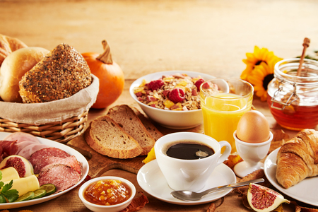 Wholesome spread of tasty fresh food for breakfast on a wooden table with an autumn theme with yellow sunflowers and pumpkins Banque d'images - 108225850
