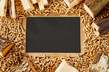 Single blackboard surrounded by light brown frame and many small wooden pegs next to chopped timber logs