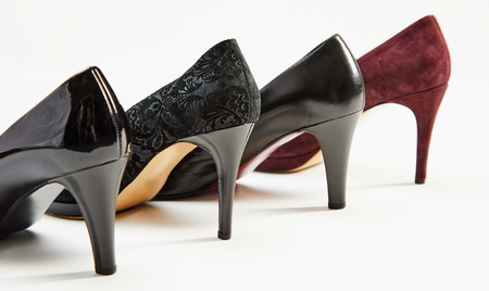 Stiletto heels on a row of elegant black and maroon leather ladies shoes arranged diagonally on white with copy space Imagens