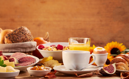 Side view of multiple platters of food and drink including cereal and juice sitting in front of wooden background