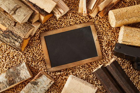 Overhead view of framed vintage blank blackboard surrounded by chopped wood logs and stacks of tiny pellets Stockfoto