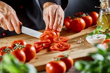 Chef cortando tomates maduros frescos en una tabla de cortar rodeada de ingredientes para la cocina italiana y mediterránea en un primer plano de sus manos