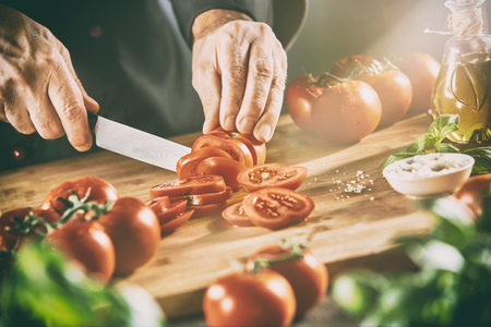 Chef slicing tomatoes on a wooden chopping board surrounded by fresh ingredients and condiments for Italian cuisine in a ray of sunlight
