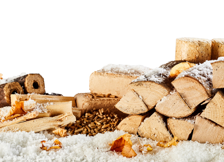 Winter wood supply with split dried logs, bricks and pellets of compressed sawdust under a sprinkling of fresh winter snow isolated on white with copy space