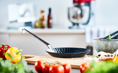 Small frying pan or skillet on a wooden chopping board surrounded with fresh salad ingredients and a pestle and mortar with herbs in a low angle view Stock Photo