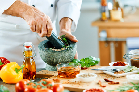 Man in chefs outfit using mortar and pestle to grind food in small pot next to tiny bowls of herbs and multiple vegetables 写真素材