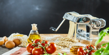 Noodle machine sitting next to bottle of olive oil and pile of raw eggs near red tomatoes sitting on cutting board