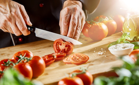 Light shining on cutting board as male chef slices tomatoes with sharp knife next to tiny bowl of salt Reklamní fotografie