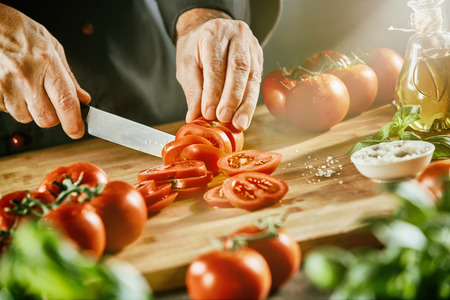 Adult male cook chopping bright red tomatoes on cutting board next to basil leaves and small white bowl of salt