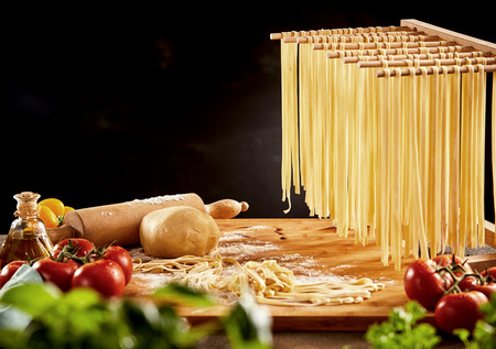 Cooked noodles hanging on wooden rack over cutting board with rolling pin behind foreground vegetables
