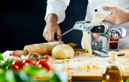 Male cook feeding dough into shiny metal machine sitting on wooden cutting board next to tomatoes and leafy green herbs
